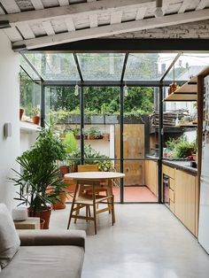 A steel and glass structure wraps one end of the apartment, adding the illusion of greater space to the 720-square-foot home.