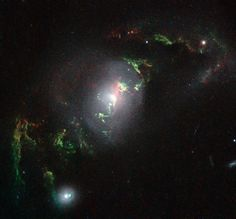 This new NASA/ESA Hubble Space Telescope image shows ghostly green filaments, lying within galaxy UGC 7342. This filament was illuminated by a blast of radiation from a quasar — a very luminous and compact region that surrounds the supermassive black hole at the centre of its host galaxy.  Its bright green hue is a result of ionised oxygen, which glows brightly at green wavelengths. http://www.spacetelescope.org/images/heic1507e/