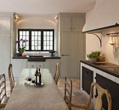 belgian kitchens - range wall of an off white kitchen with large range wall - Joris van Apers via Atticmag