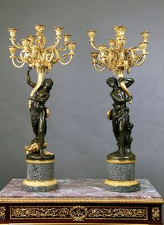 A Pair of Late 19th Century Two Tone Bronze Nine Light Candelabra After Clodion - Each cast as a female and a male figure from a bacchanale upholding eight scroll branches with a central branch in the form of a quiver, on a bronze mounted circular base of granite.