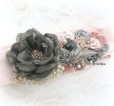 Made Upon Request  This sash was designed specifically for a lovely customer who was looking for a piece in soft pinks and light and dark greys to adorn her wedding gown.  Beautifully handmade flowers in the desired colors, along with a gorgeous crystal and pearl upcycle brooch, sparkly jewels and my signature cluster of pearls and crystals make this sash a romantic and elegant heriloom piece. The applique has been attached to a taffeta sewn belt in a very light shade of pink. The belt…
