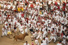 A reveler is tossed by a steer during a celebration held at the bullring after the running of the bulls on July 7, 2015.