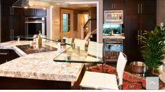 Light granite, dark cupboards, glass breakfast bar