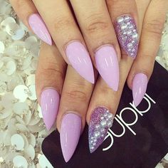 light pastel violet nail polish, smooth and shiny, with silver pearl stickers, and violet glitter, on stiletto acrylic nails