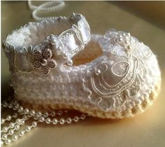 Embellished with hand-sewn bridal lace, tiny pearls , translucent sequins and satin ribbon.  Crochet in Pure white yarn for upper shoe and off white for sole.  by TippyToesbabyshoes, $40.00