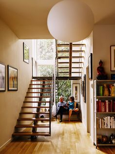 Louis did much of the woodworking in the house, including the fabrication of the <br>white oak stair treads. The ironwork was crafted by Alex and Gio Welding. A Glo Ball pendant by Jasper Morrison for Flos hangs in front of the staircase.