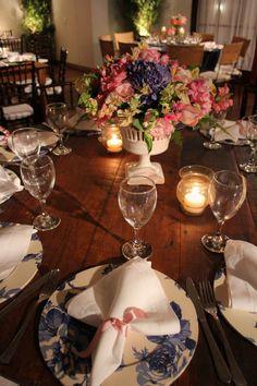 Detalhe da mesa de convidados com sousplats de tecido e arranjo super delicado no centro da mesa. Decoração de casamento nas cores azul e rosa. Clube Caiçaras - A&K decoração de eventos