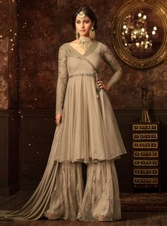 Enchanting beige wedding sharara online which is crafted from net fabric with exclusive embroidery and stone work. This stunning designer sharara comes with santoon bottom and santoon and net dupatta. Pakistani Dresses, Indian Dresses, Indian Outfits, Pakistani Couture, Pakistani Bridal, Indian Bridal, Indian Designer Outfits, Designer Dresses, Sharara Suit