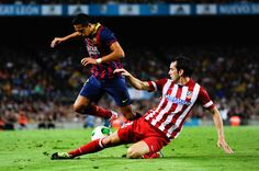 Alexis Sanchez of FC Barcelona duels for the ball with Diego Godin of Atletico de Madrid during the Spanish Super Cup second leg match between FC Barcelona and Atletico de Madrid at Nou Camp on August 28, 2013 in Barcelona, Catalonia.
