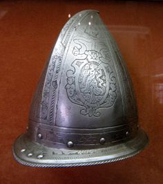 Chateau-Ecouen- CABASSET (casque de la Renaissance) Ce mot vient de l'Espagnol capacete. La calote est munie d'un rebord étroits et se termine par une pointe saillante à son sommet (comme la queue d'une poire). La plupart des cabassets étaient lisses, mais de rares décorations (gravures ou rivets) sont parfois présentes.