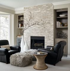Transitional living room in with beige walls, carpet and a standard fireplace. built-in cabinetry · casual elegance · fur ottoman · leather armchair · neutral · Side Tables & End Tables · Sophisticated · tile wall · vases