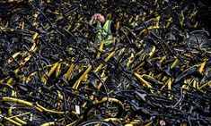 A mechanic from bike share company Ofo stands amongst damaged bicycles needing repair in Beijing.