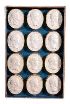 A set of Italian plaster intaglio casts representing the Twelve Caesars,   late 18th century, arranged in a rectangular deal case, the cover interior with a printed paper list of   LI DODICI CESARI,   and with a further label stating that the casts are after Pietro Bracci, the intaglios 6cm long, the box 3.5cm high, 26cm long, 17cm wide