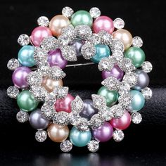 Multicolored crystal and simulated pearl wreath shaped brooch inset in silver toned zinc alloy base. This is a lovely brooch which looks like more than one brooch stacked on top of one another.  Measures 2.2 CM across    xxxxxxxxxxxxxxxxxxxxxxxxxxxxxxxxxxxxxxxxxxxxxxxxxxxxxxxxxxxxxx    Please feel free to contact me with any question or concerns you may have such  as insurance, packing, shipping cost, combined shipping or more details on the item listed.  If you need your item shipped…