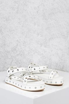 A pair of faux leather flatforms featuring allover button stud embellishments, an open toe, and an adjustable ankle strap.