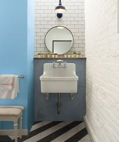 Bathroom sink area with subway tile, brick wall and black and white striped floors