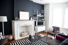 Modern Living Room with Painted fireplace, Built-in bookshelf, Stockholm flatwoven area rug, Laminate floors, flush light