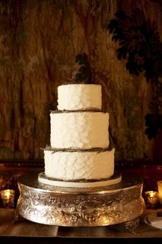Three-tiered cream wedding cake with golden brown decorative accents by Party Flavors.