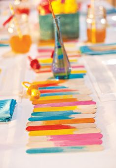 A DIY watercolor popsicle stick runner adds pop to a party table.