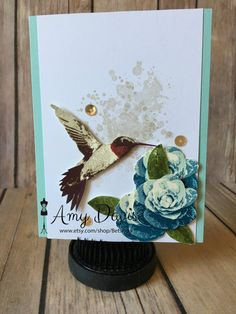 This any occasion card has a very pretty hummingbird and roses as the focal point. The color theme is pool party from Stampin Up!. The hummingbird and roses are both 3-step stamps, then I added splatter spots in the background and then gold sequins to set everything off. Some of the rose grouping is raised to add dimension. There is not a sentiment on the front but can add one if you like. The inside is blank and ready for your handwritten sentiment or I can stamp a sentiment of your choice…