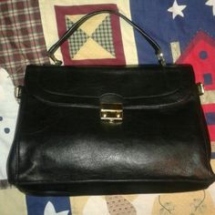 """New York & Company Black Briefcase Hangbag Purse Very nice and elegant looking black briefcase handbag purse. It has a gold tone closure in the front. It has some scratches and wear on it. Is not real leather. On the sides you can unhook the strap and make the bag wider. The first 3 pics the bag is somewhat stuffed. Inside its clean with a zip compartment and on the other side two pockets. Size is 13.5"""" wide, 10"""" long and handle drop is 5.5"""". This bag has no strap. Is just a handheld or on…"""
