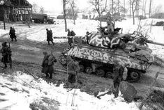 Un char américain Sherman M4A3 (Canon de 76mm)-camouflage d'hiver et les soldats du déménagement 75e Division d'infanterie le long d'une route de campagne dans les Ardennes, entre décembre 1944 et janvier 1945.