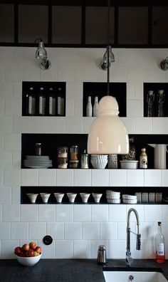 Sq. white tiles, subway layout, inside shelves painted black. French designer