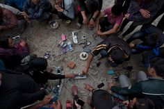 Nepalese villagers charge their cell phones in an open area in Kathmandu, Nepal on April 27, 2015.