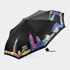 New York City Skyline Color-Changing Umbrella. This umbrella features the profile of New York City's bustling skyline along its perimeter. The exterior changes from white to bright shades of green, yellow, blue, pink, and orange when wet, creating a vibrant cityscape on a rainy day.