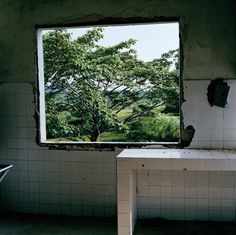 Tim Hetherington LIBERIA. Tubmanburg. June 2003. A bombed-out window in the derelict central hospital of Tubmanburg reveals the green bush of the countryside.