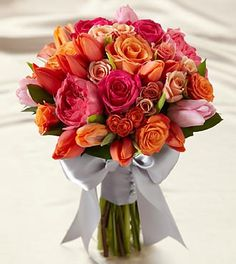 The FTD® Sunset Dream™ Bouquet bursts with sun-drenched color to captivate and charm at every turn. Orange tulips, peach spray roses, pink garden roses, fuchsia roses, light orange tulips, light pink