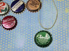 Bottle Cap Necklace.   bottle caps  A small nail  A hammer  A jump ring  Needle-nosed pliers  A piece of ribbon or cord  A surface to hammer on, such as a self-healing mat or a piece of recycled corrugated cardboard (the sturdy, thick kind of cardboard)