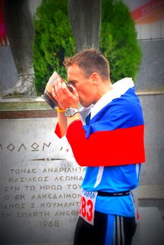 Lojze Primožič drinking from a cup of vitory at the finish of Spartathlon 2013