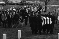 Mrs. Evelyn Grubb, of Colonial Heights, Va., left, follows her husband Wilmers coffin at Arlington National Cemetery, Thursday, April 4, 1974, Washington, D.C. Col. Grubb's name was released by the Democratic Republic of Vietnam as one of the prisoners of war who died in captivity. Mrs. Grubb holds the hands of two of her sons, Roy, 7, right, and Stephen, 10