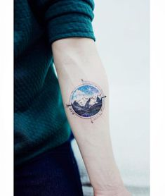 An unusual circular tattoo of a mountainous landscape and a compass around it
