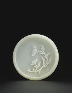 PALE CELADON JADE BRUSH WASHER QING DYNASTY, 18TH CENTURY of circular form, with countersunk base and rounded sides incurved at the rim, the interior crisply carved in relief with a single spray of poppy flowers issuing the characteristically jagged leaves and two delicately petalled blooms, the stone softly mottled with a pale russet inclusions Diameter 5 1/4  in., 13.2 cm. | Sotheby's