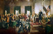 An oil-on-canvas painting of the 39 delegates sitting and standing in Independence Hall. George Washington is standing upright and looking out over the delegates.