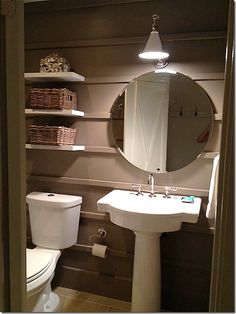 A more dramatic bathroom with a simple vanity sink was added, along with a new pendant light and hanging shelves.