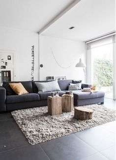 Love this living room. Warm, grey, neutral, white. And wooden stumps as coffee tables!