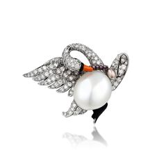 A lovely brooch crafted in platinum displays the figure of a swan with an open wing, featuring a natural freshwater pearl measuring approximately 13.43 mm, enhanced by round brilliant and single-cut diamonds weighing a total of approximately 1.65 carats; accented by cabochon cut rubies for eyes, enhanced by orange and black enamel details on the bill and foot; swan fit with its own miniature pearl necklace; brooch is fastened with a single pin stem and c-catch; measures 1-1/2 x 1-1/8 inches;
