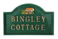 A pretty green house sign with a cottage motif in the arch. Lovely to look at.