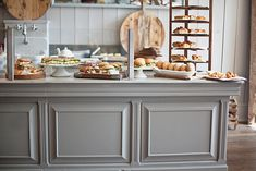 Love the grey of the counter/island vs the camel color of the pastries,bread, and wood boards
