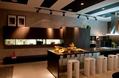 Espaço Gourmet com banquetas baixas. A cozinha além de moderna possui iluminação indireta.   https://www.homify.com.br/livros_de_ideias/37407/10-estilosas-banquetas-para-sua-cozinha