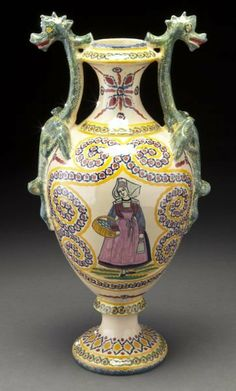 "Henriot Quimper pottery ewer with dragon handles and a painted scene depicting a Breton woman carrying a basket of eggs, accented by an ivoire corbeille design. Base signed ""HenRiot Quimper 75"". 16''H, Circa - Second quarter 20th C."