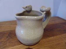 Studio pottery milk jug with hedgehog on rim. Signed 'RF'