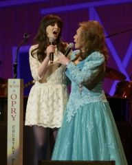 Loretta Lynn and Zooey Deschanel on the stage of Opry Country Classics at the Ryman