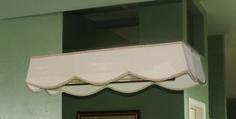Shade made to cover outdated Hollywood style light bars in bathroom.