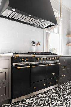 A Lacanche Range sits on a black and white cement floor tiles between black shaker drawers adorned with brass pulls and a white quartz countertop.