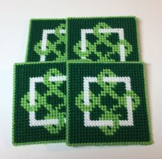 """This set of four coasters features a Celtic-style emblem in the center. The coasters are worked in two shades of green and white. The coasters, which measure approximately 4.25"""" square, are backed wit"""