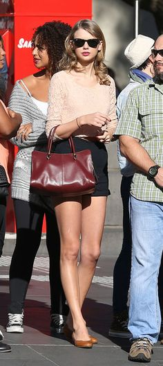Taylor Swift in high-waisted shorts and a lace top. Femme yet cool.